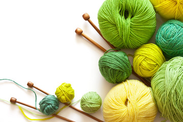 Crafts and Hobbies. Green and yellow balls of yarn for hand knitting and wooden needles on a white background. Empty space for text. Flat lay, close up, macro