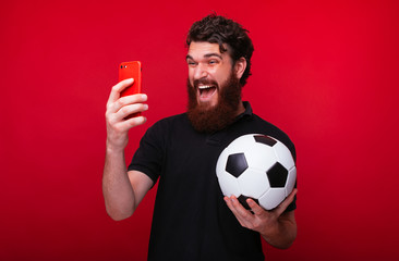 Photo of bearded guy, holding a soccer ball, screaming and watching game online, over red background