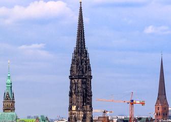 Hamburg, Germany-The ruin of the memorial church St. Nikolai (peace memorial) at Hopfenmarkt in Hafen city quarter. City Hall on the left, St. Petri Church on the right.