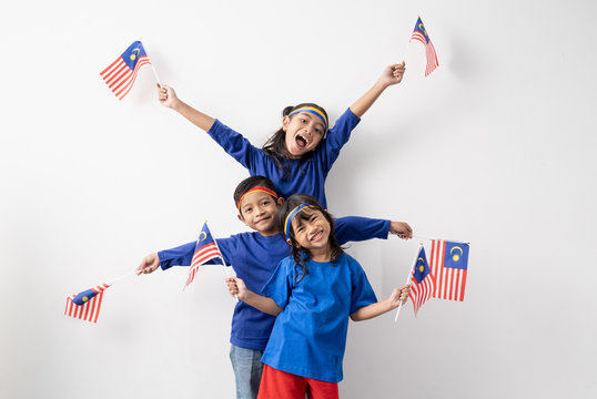 happy excited malaysian kids with malaysia flag over white background