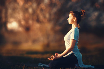 Woman meditating in the rays of the setting sun. Wall mural