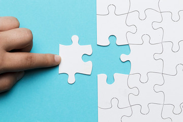 Human finger touching white puzzle piece on blue background