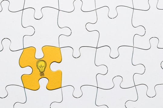 Idea icon on yellow puzzle piece connected with white grid puzzle backdrop