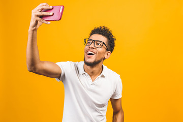 Image of happy young african american man posing isolated over yellow background take a selfie by phone.
