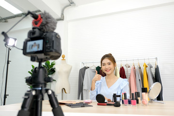 Young asian beauty blogger recording video tutorail make up with beauty products at home studio, beauty and fashion lifestlye blog