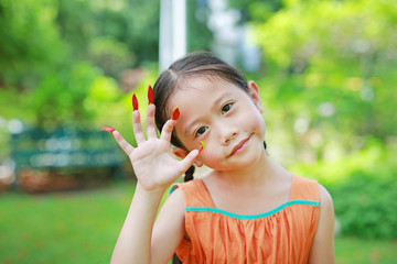 Portrait of little Asian child girl playing with Stick the flower petals to the nail like a tiger or wild animal in the garden.