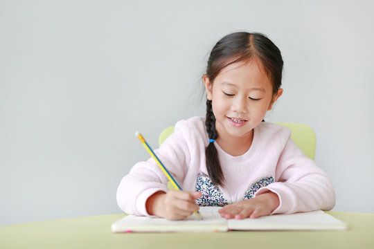 Happy little Asian child girl writes in a book or notebook with pencil on table in classroom against white background.