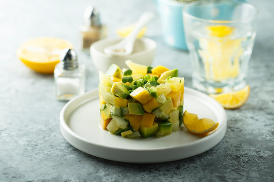 Delicious mango avocado salad on white plate