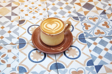 cup of latte coffee on mosaic tile background
