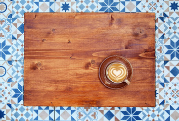 cup of latte coffee on wooden table top view, mosaic tiles floor