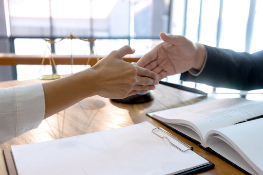 Lawyer or judge  with gavel and balance handshake with client