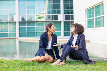 Cheerful businesswomen sitting on lawn. Smiling barefoot multiethnic female colleagues sitting together on grass and talking. Communication concept