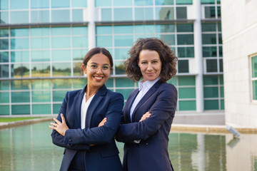 Team portrait of happy confident businesswomen posing with hands crossed. Two women wearing office suits, standing outside and smiling at camera. Teamwork concept