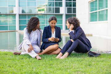 Barefoot businesswomen using smartphone. Focused multiethnic female colleagues sitting on green lawn and using cell phone together. Technology concept