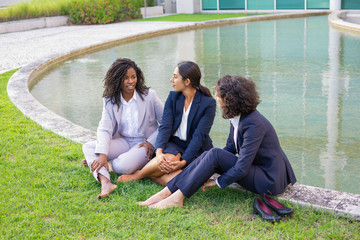 Cheerful businesswomen resting on grass. High angle view of smiling multiethnic female colleagues talking while sitting together on green lawn. Coworkers concept