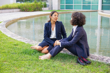 Barefoot female colleagues sitting on grass. Professional multiethnic businesswomen in formal wear sitting on green lawn and talking. Communication concept