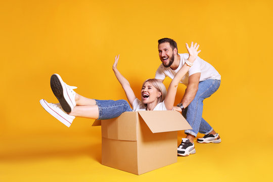 Young married couple moving into a new home. Attractive blonde woman sitting in cardboard box while bearded man pushes her. Newely weds fooling around. Isolated yellow background, copy space, close up