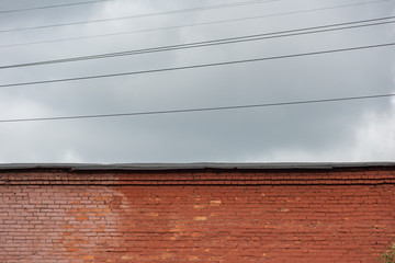 Industrial brick wall with roof and wires