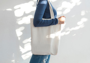 Girl is holding bag canvas fabric for mockup blank template on sunlight background.  global warming concept. Wall mural