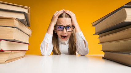 Stressed Elementary Schoolgirl Clutching Head Sitting Between Book Stacks