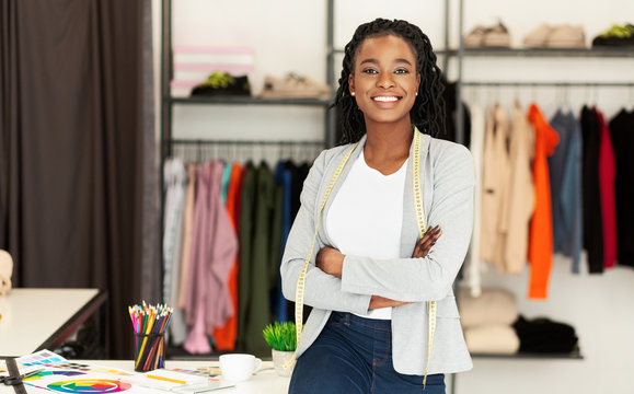 Successful African American Fashion Designer Smiling At Camera In Boutique