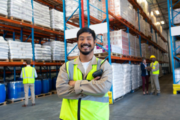 Male worker standing with arms crossed and looking at camera in warehouse