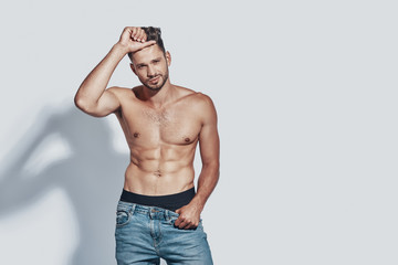 Handsome young shirtless man looking at camera and taking off his jeans while standing against grey background