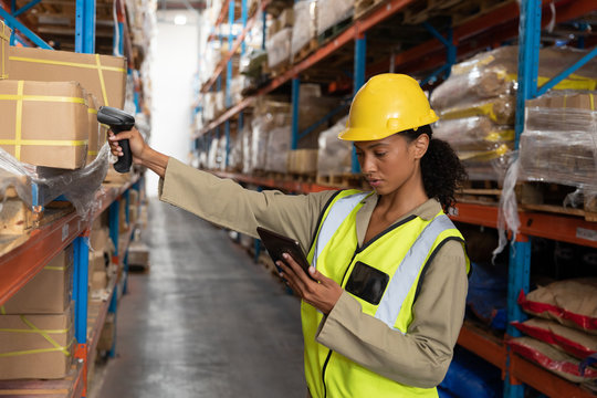 Female worker scanning package with barcode scanner while using digital tablet in warehouse