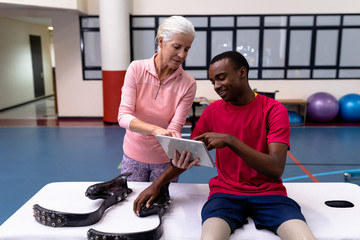 Active senior female trainer and disabled man discussing over digital tablet in sports center