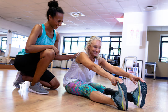 Female trainer assisting disabled active senior woman to exercise in sports center