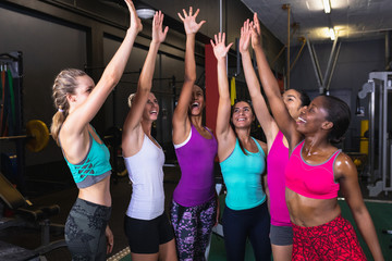 Female athletic team giving high five to each other in fitness center