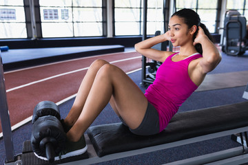 Female athletic exercising on ab bench in fitness center