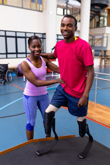 Physiotherapist helping disabled man walk with prosthetic leg on ramp in sports center