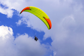 Bright yellow paraglider with orange inserts on the sky background