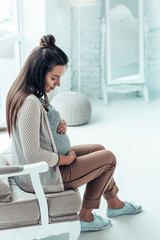Charming longhaired pregnancy sitting alone at home