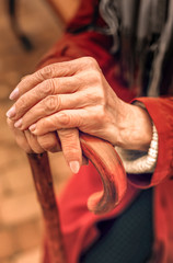 Close up of hands of an elderly woman leaning on cane