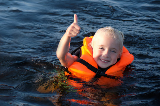 Happy blond little girl swimming in orange life jacket in the sea. girl shows thumb up