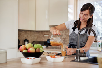 Beautiful smiling Caucasian woman in apron standing in kitchen and pouring fresh smoothie into glass.