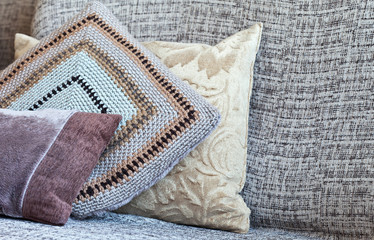 Handmade sofa cushions: one crocheted from the remains of woolen yarn, two sewn from pieces of soft fabric. Crafts, hobbies, household