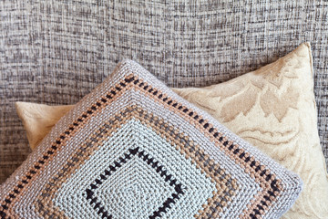 Two handmade sofa cushions: one crocheted from the remains of woolen yarn, the second sewn from soft plush fabric. Needlework, hobbies, home interior