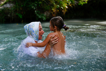 Woman with a girl dip in cold waters of Golubaya Krinitsa, (Blue Spring) during celebration of Orthodox Honey Savior, which is also called the Savior on Water, near the town of Slavgorod