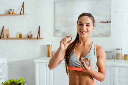 happy sportive woman holding almond and smiling at home