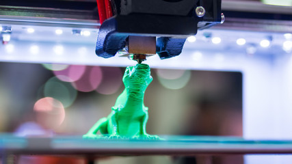 Print head of 3D printer machine printing plastic model of green toy lizard at modern scifi technology exhibition. 3D printing, additive technologies, 4.0 industrial revolution and futuristic concept