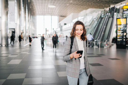 Young girl at the airport walks, looking at her smartphone, smiling.