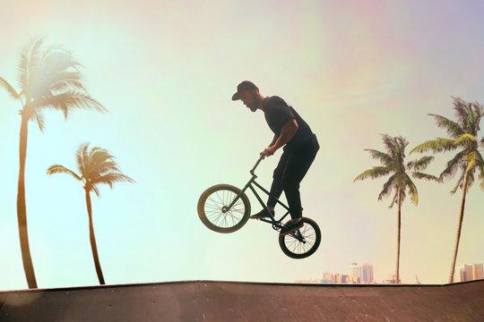 BMX rider is performing tricks in skatepark on sunset.