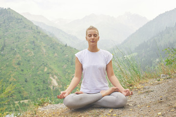 In de dag Ontspanning Sport girl doing yoga in mountains beautiful landscape. Young woman leads healthy lifestyle, meditates, relaxes lotus position in bright sportswear on nature
