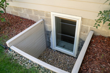 Fototapeta Exterior view of an egress window in a basement bedroom. These windows are required as part of the USA fire code for basement bedrooms