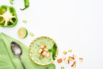 Fotobehang In het ijs top view of delicious creamy green vegetable soup served with napkin and spoon isolated on white
