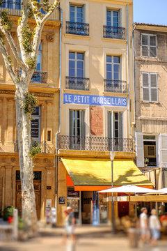 AIX-EN-PROVENCE, FRANCE - JUL 17, 2014: Le petit marseillais inscription on the building in the central pedestrian street of Aix-En-Provence on a summer day with pedestrians