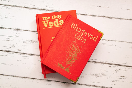 Holy Bhagavad gita and The Holy Veda the oldest scriptures of Hinduism on wooden textured background